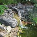 LOGO_naturnahe Teichgestaltung mit Muschelkalk-Trockenmauerwerk und einem Muschelkalk-Findling als Quellstein